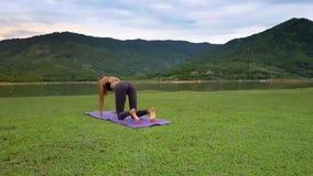 Flycam gira alrededor de la muchacha que hace yoga contra el lago verde
