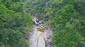 Flycam hangs above gorge with small stream among jungle. Flycam hangs above rocky gorge with small mountain stream among pictorial green forestry landscape stock video footage