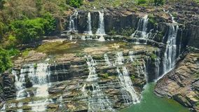Flycam Hangs above Narrow Waterfalls Running from Rocks. Flycam hangs above fantastic narrow powerful waterfalls running from rocks among tropical highland stock video footage