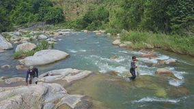 Flycam Shows Guy Collecting Net to Throw into River among Rapids stock video footage