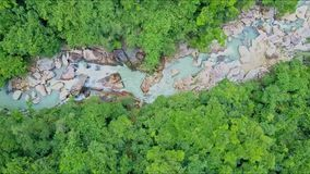 Flycam moves down stony river among tropical jungle stock video footage