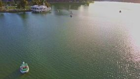 Flycam Moves Fast over Amazing Quiet Lake Water with Boat. Flycam moves fast over amazing quiet lake water with white swan catamaran against bright sunset sky stock video