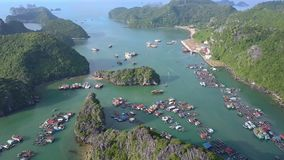 Flycam Moves over Tranquil Ocean Bay and Floating Village. Flycam moves over amazing tranquil ocean bay and floating village among rocky islands covered with stock video