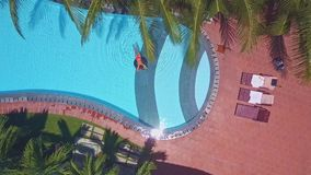 Flycam moves to folding chairs and woman in blue pool. Flycam moves slowly to folding chairs on wooden deck near swimming pool and woman on blue water stock video footage