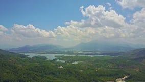 Flycam muestra el río de la selva de la visión panorámica contra las montañas
