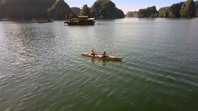 Flycam muestra a la muchacha Guy Row Kayak contra el barco y Hilly Islands almacen de video