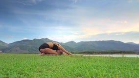 Flycam muestra a la muchacha que se sienta en actitud de la yoga contra Hilly Landscape