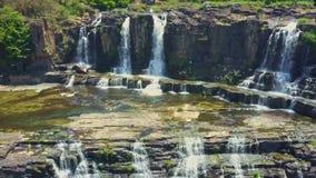 Flycam muestra la vista de cascadas contra rocas en las zonas tropicales