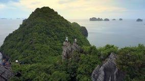 Flycam muestra a los turistas felices que agitan las manos en la montaña escarpada grande metrajes