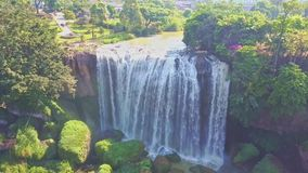 Flycam Opens View of Waterfall against Plants Boulders Sky stock footage