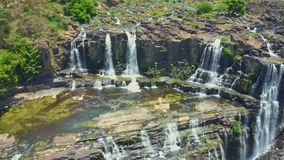 Flycam opens view of waterfalls against rocks tropical plants stock footage