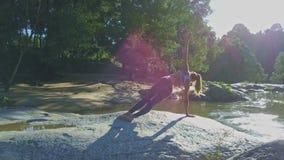 Flycam Pokazuje dziewczyny mienia joga pozę przeciw Pokojowej rzece zdjęcie wideo
