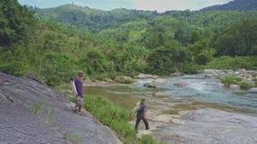 Flycam Pokazuje mężczyzna Chodzi na Skalistym brzeg rzeki przeciw średniogórzu zdjęcie wideo