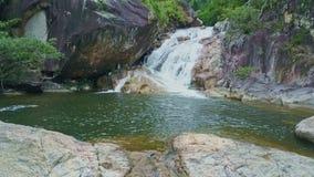 Flycam quita de la cascada que corre en el lago contra selvas