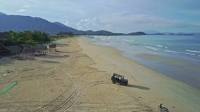 Flycam Removes from Military Jeep Standing on Beach to Sea. Flycam removes from large powerful military jeep standing on beach to azure ocean with wave surf stock video