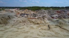 Flycam rises above clay pit by forest under blue sky. Flycam rises above brown and grey old clay quarry with canyons and clefts near forest under blue sky with stock video footage