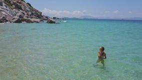 Flycam Rotates around Girl in Azure Sea near Rocky Beach stock video