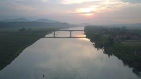 Flycam ruchy od wysokości tęsk most nad szeroką rzeką przy zmierzchem zdjęcie wideo