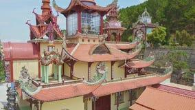 Flycam se acerca a la pagoda del templo que pasa el árbol de abeto en yarda metrajes