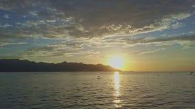 Flycam se déplace au-dessus de l'océan fusionnant avec le lever de soleil d'or sur l'horizon