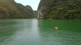 Flycam se déplace au-dessus de la baie tranquille avec des sportifs naviguant sur des kayaks clips vidéos