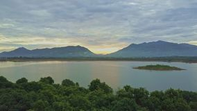 Flycam se déplace au-dessus du lac paisible contre Hilly Landscape Sunrise