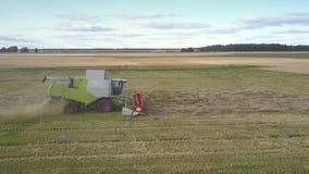 Flycam se mueve cerca de la cosechadora que recolecta el trigo que sale de la paja metrajes