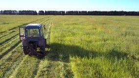 Flycam se mueve cerca del tractor con el granjero en hierba de siega de la cabina almacen de metraje de vídeo