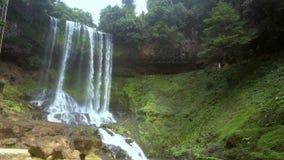 Flycam se mueve desde el banco de la hierba a rocoso contra la cascada en reserva de naturaleza metrajes