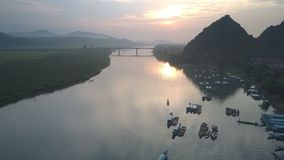 Flycam se mueve desde la puesta del sol perfecta reflejada en el agua de río almacen de metraje de vídeo