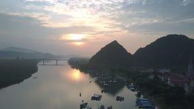 Flycam se mueve a la reflexión de la puesta del sol que sorprende en el río tranquilo metrajes