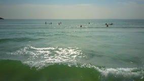Flycam se mueve a lo largo de sunpath que destella a las personas que practica surf en el océano metrajes
