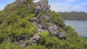 Flycam Shows Beautiful Cliff Island and Woman among Rocks. Flycam shows beautiful old cliff island covered with tropical plants and slim blonde woman among rocks stock video