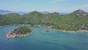 Flycam shows hilly peninsula surrounded sea under clear sky stock footage
