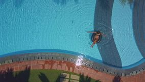 Flycam shows hotel pool with lady sitting on buoy