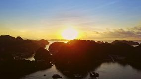Flycam Shows Beautiful Tropical Sunrise above Quiet Ocean. Flycam shows beautiful tropical sunrise above large quiet ocean bay and steep rocky islands stock video footage