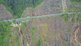 Flycam shows bus on road over cliff with beautiful waterfalls stock video footage