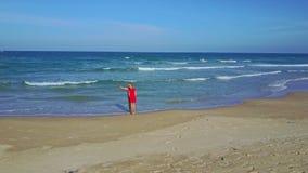 Flycam shows couple making selfie on sand ocean beach stock video