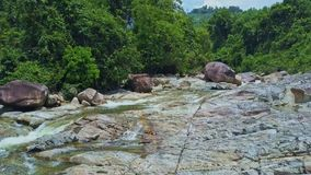 Flycam Shows Crystal Creek Streaming Through Rocky Land. Flycam shows crystal clear creek streaming through rocky land among tropical plants against blue sky stock video footage