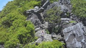 Flycam Shows Girl with Ponytail Stands among Stones on Island stock video footage