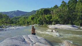Flycam Shows Girl Taking Photos against Tropical Plants Hills. Flycam shows girl taking photos among river rapids against tropical plants and hills on sunny day stock video footage