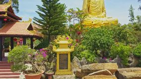 Flycam Shows Golden Buddha Sculpture among Tropical Plants. Flycam shows famous golden Buddha sculpture located on religious temple territory among tropical stock video footage