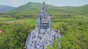 Flycam Shows Huge Sculpture among Trees against Hills. Flycam shows huge rocky sculpture located on temple territory among trees against majestic hilly landscape stock footage