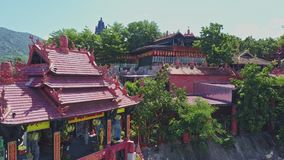 Flycam Shows Pagoda Buildings against Distant Hill Sky. Flycam shows beautiful ancient pagoda buildings under scorching sun against distant hill and blue sky stock video footage