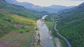 Panoramic view rocky river near road between hilly landscape. Flycam shows panoramic view long rocky river streaming near road between hilly landscape and stock video footage