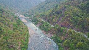 Flycam view rocky river near road between tropical plants. Flycam shows panoramic view long rocky river streaming near road between tropical different plants stock video