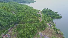 Flycam Shows Quiet River with Tropical Forest and Road on Bank. Flycam shows amazing view wide quiet river with green wild fresh tropical forest and modern road stock video footage