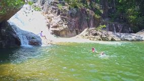 Flycam Shows Tourists Swimmming in Lake at Waterfall stock video footage