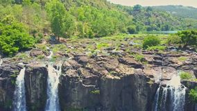 Flycam Shows Waterfall Streams from Cliff against Jungle stock footage