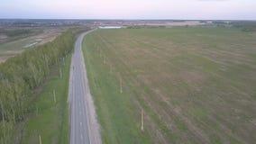 Flycam si muove lungo la strada principale fra il campo e la cinghia della foresta video d archivio